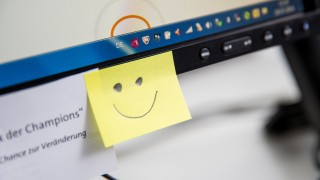 Smiley Post It an einem PC Arbeitsplatz